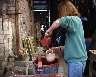 Meredith glazing a large jug at an Irish pottery in County Cork Ireland