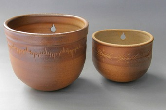 2 wodfired wall plant pots with design
